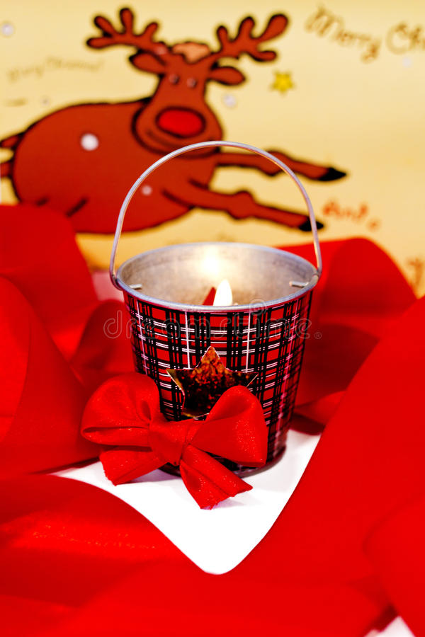 Red ribbon, candle and christmas card