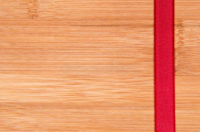 Red ribbon. On wood background stock photo