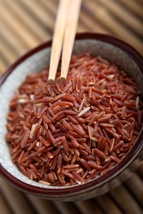 Red rice. Bowl of red rice from Thailand and chopsticks stock photo