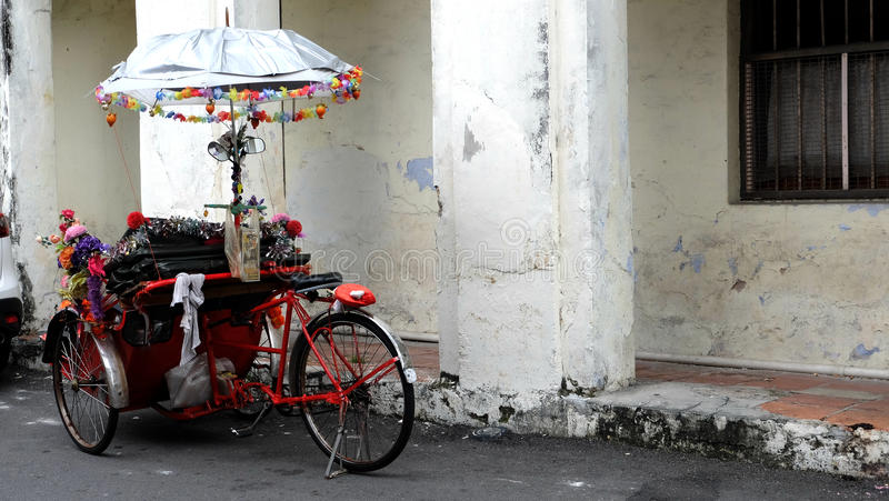 Red rickshaw with an umbrella. Red rickshaw is still commonly seen in George Town, Penang, Malaysia which is a well-known as UNSECO heritage site stock images
