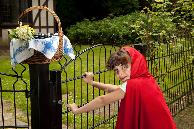 Red riding hood at gate royalty free stock image