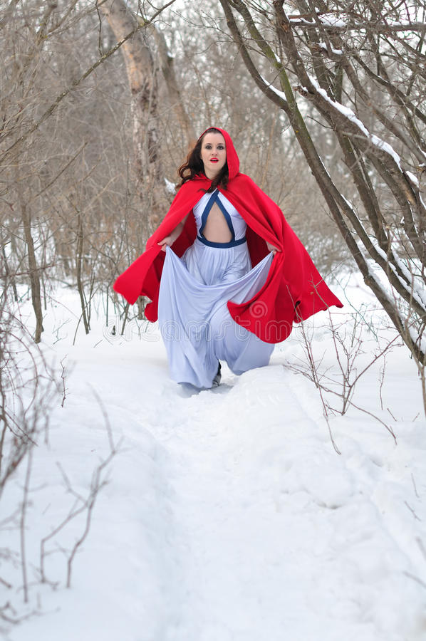 Red Riding Hood runs on a footpath. Little Red Riding Hood runs in the winter woods royalty free stock photography