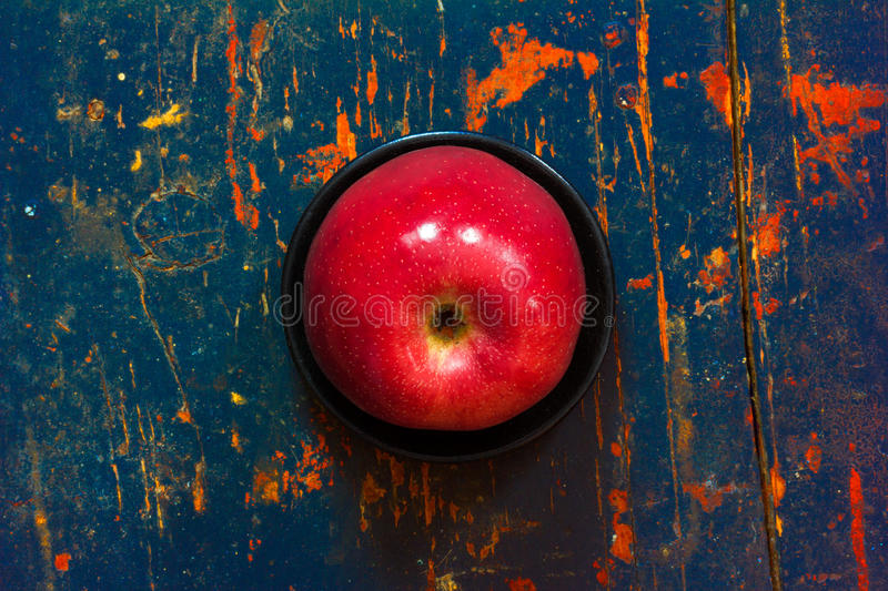 Red ripe apple in a black saucer on old background royalty free stock photos