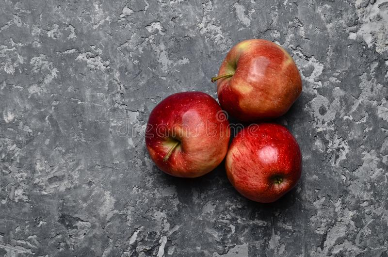 Red ripe apples on a concrete table. Fresh fruits. Loft and rustic style. stock photo