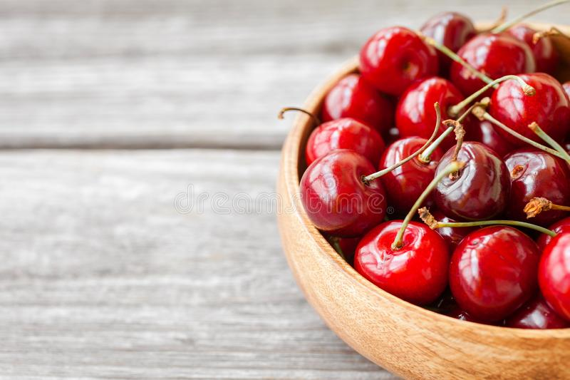 Red ripe cherry berries in wooden bowl. Food background stock photography