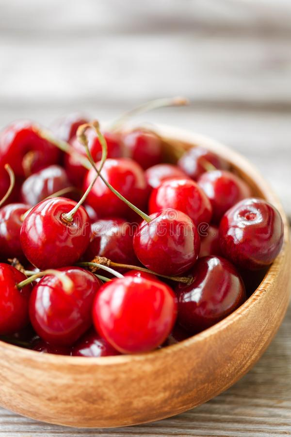 Red ripe cherry berries in wooden bowl. Food background royalty free stock photo
