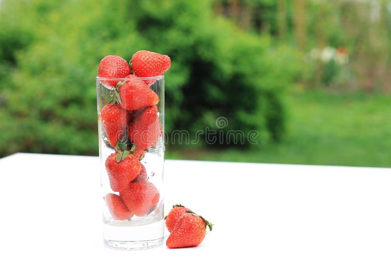 Strawberries in glass bowl with blurred natural green background stock photography
