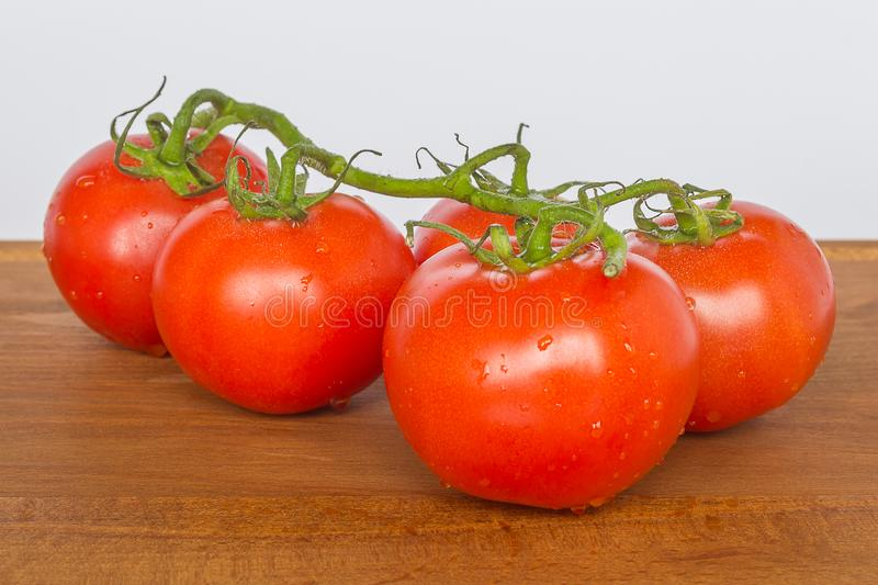 Red ripe tomato branch on a brown wooden cutting board on a neutral background. Healthy eating and vegetarian food concept, close. Up, selective focus stock photos