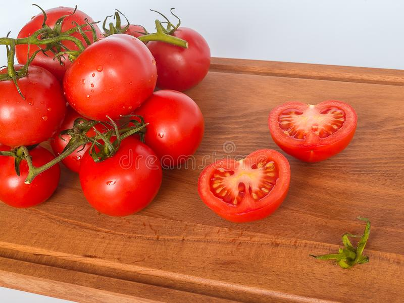 Red ripe tomato branch on a brown wooden cutting board on a neutral background. Healthy eating and vegetarian food concept, close. Up, selective focus stock images