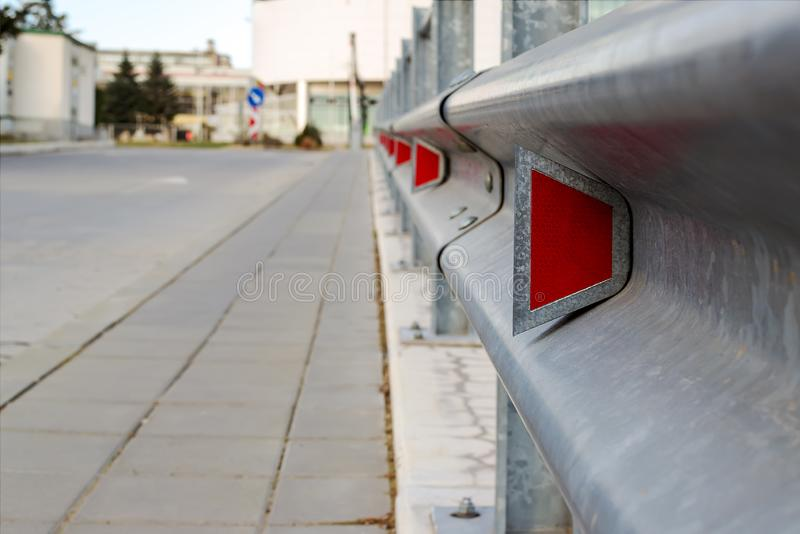 Red road reflectors along the road. Zinked or galvanized metal road fencing of barrier type, close-up. Road and traffic safety. Selective focus with shallow stock photography