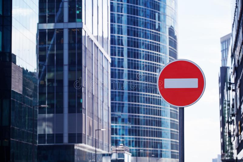 Red road stop sign or brick on city skyscrapers business center blurred background close up, entrance prohibition royalty free stock images