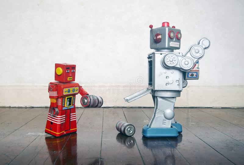 Red robot helping big silver robot. With a power problem stock image