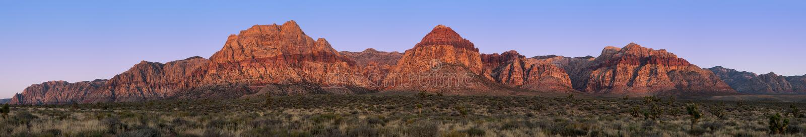 Red Rock Canyon pano. Panorama of Red Rock Canyon, Nevada, USA, at sunrise with yacca and Joshua trees in the foreground royalty free stock images
