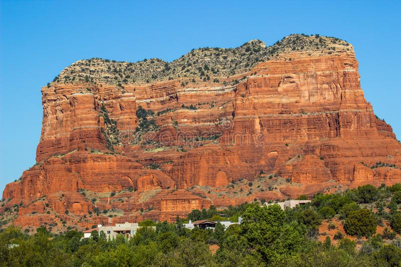 Red Rock Mountain With Layers Overlooking Houses In Arizona Desert. Red Rock Mountain With Layers Overlooking Houses In The Southwest Arizona Desert stock photo