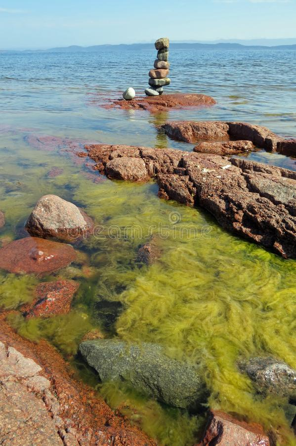 Red rock plateaus and the sea with lots of green seaweed in front of two Zen stone towers at beautiful Storsandstranda, Sweden, Eu. Storsand is a quiet, mainly royalty free stock photos