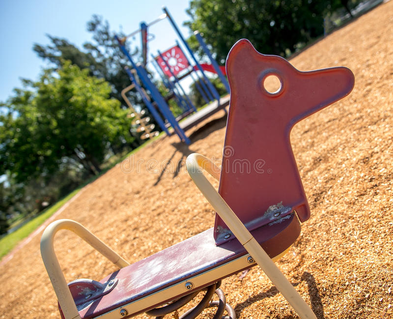 Red rocking horse in summer with children's jungle gym and park stock images