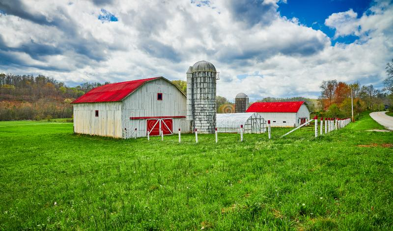 Red Roof Barn with Silo in Early Spring stock images