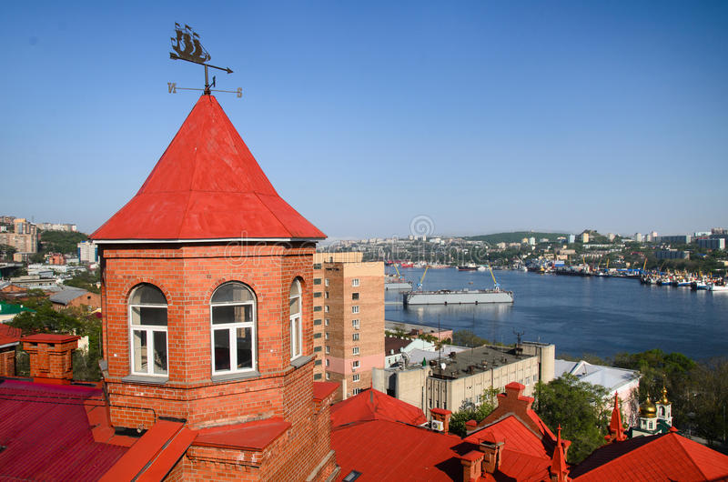 Red roof of brick building, port Vladivostok, panorama of Zolotoy rog bayl, Russia. Red roof of brick building, weathervane on tower, port Vladivostok, panorama royalty free stock photo