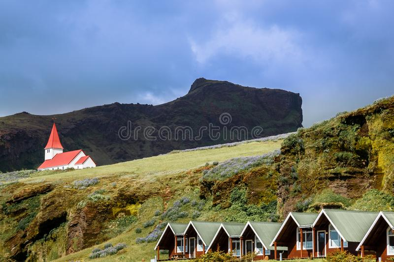 Red roof church on the hill, with summer cottages in the foreground, Vik i Myral, Iceland stock images
