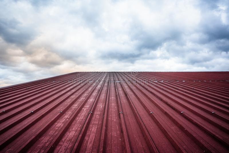 A red roof of corrugated steel pointing to the sky royalty free stock photos
