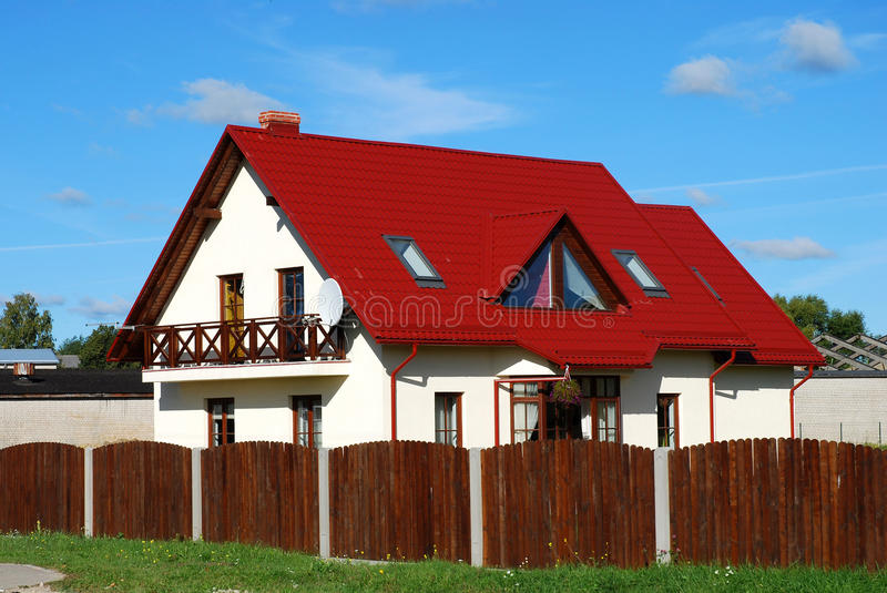 Red roof house. Private house with red tile roof and wooden fence royalty free stock image