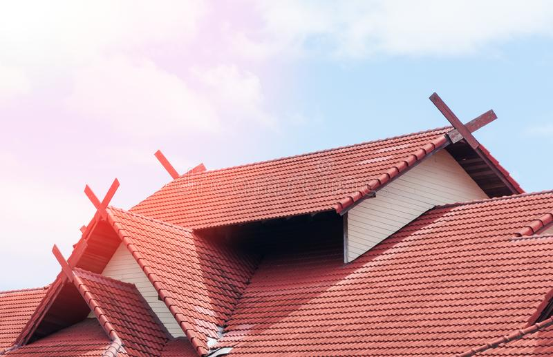Red Roof house with tiled roof on blue sky stock photos