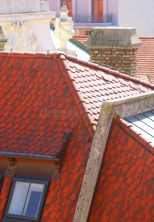Red roof with window of building and decoratins on the top of the roof in old town in Bratislava, Slovakia royalty free stock photo