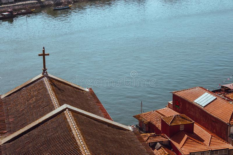 Red roofs with cross on river Douro background top view. Embankment with church roof and wooden cross in Porto, Portugal. Portuguese landscape. Summer travel royalty free stock images