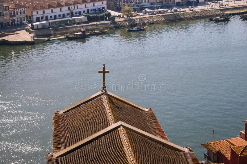 Red roofs with cross on river Douro background top view. Embankment with church roof and wooden cross in Porto, Portugal. stock image