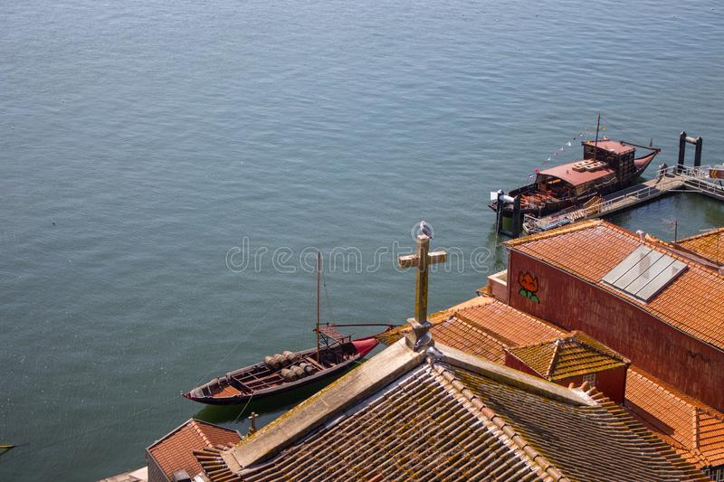 Red roofs with cross on river Douro background top view. Embankment with church roof and wooden cross in Porto, Portugal. Portuguese landscape. Summer travel stock photo