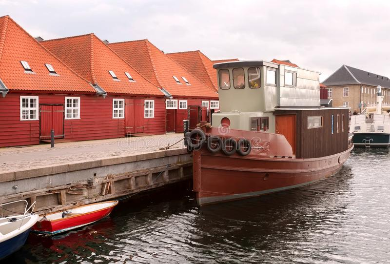 Red roofs houses near river bay with moored boats in Copenhagen, Denmark. City with water chanels.  royalty free stock photography