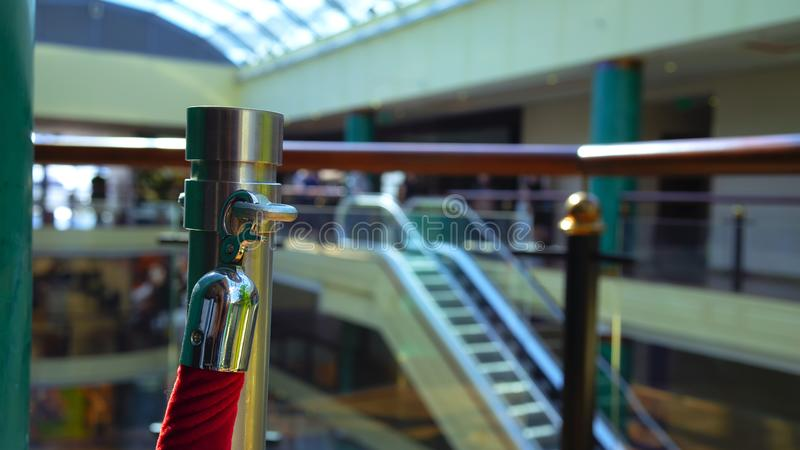 Red rope in an urban building. Red rope with chrome lock in an urban building with a glass roof and escalator royalty free stock photography