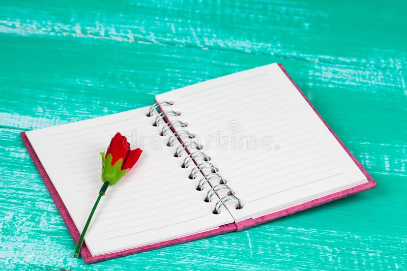 Red rose on book note in wood table. Background stock image