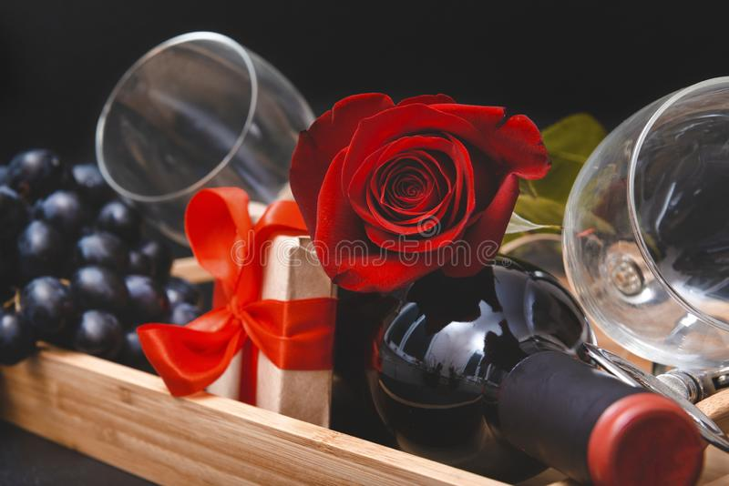 Red rose, bottle of wine, 2 glasses, dark grapes, corkscrew, gift box with ribbon on black background royalty free stock photo