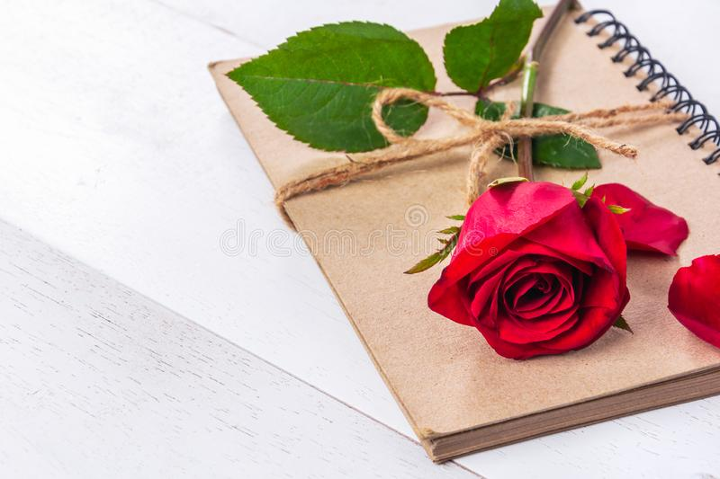Red rose on craft book. Close-up of red rose on craft book tied with hemp rope on white wooden table stock photos