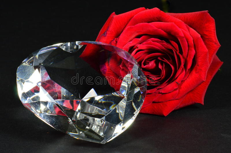 Red Rose & Crystal Heart. A red rose and crystal heart in a pleasing still life composition on a dark background royalty free stock image