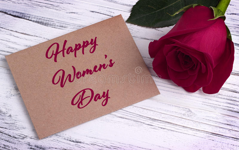 Red rose and and envelope for valentines day womens day greeting card and lettering happy women`s day english. stock image