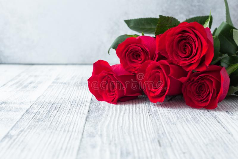 Red rose flowers bouquet on stone background Valentine`s day greeting card White wooden table stock image