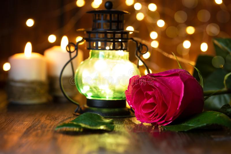 Red rose and lantern with lights on a wooden table stock photography
