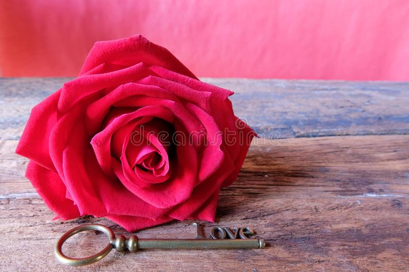Red rose and love key shape with brown paper card. Copy space for Valentine's concept. Red rose and love key shape with brown paper card. Copy space for stock photos