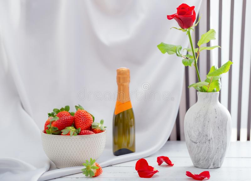 Red rose, strawberries and champagne for the celebration of women`s holidays and anniversaries.  stock images