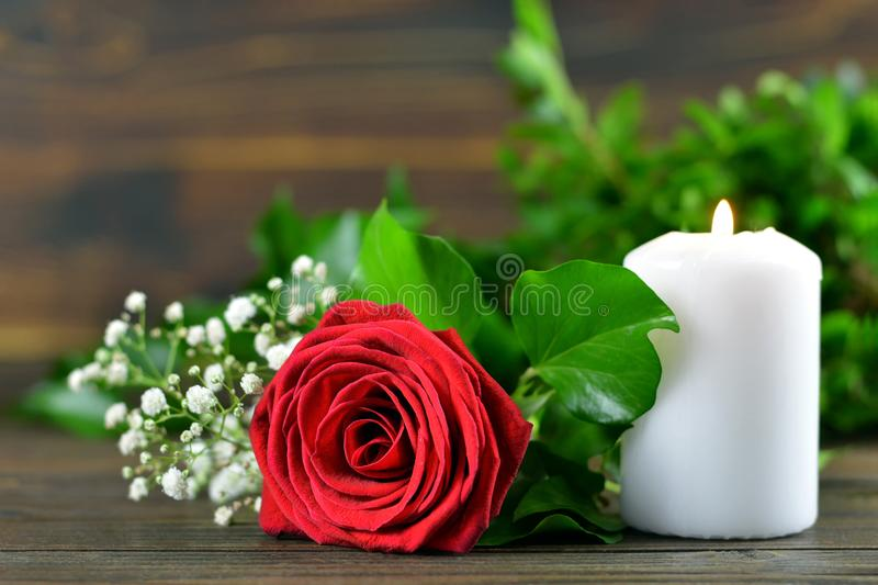 Red rose and white burning candle stock image