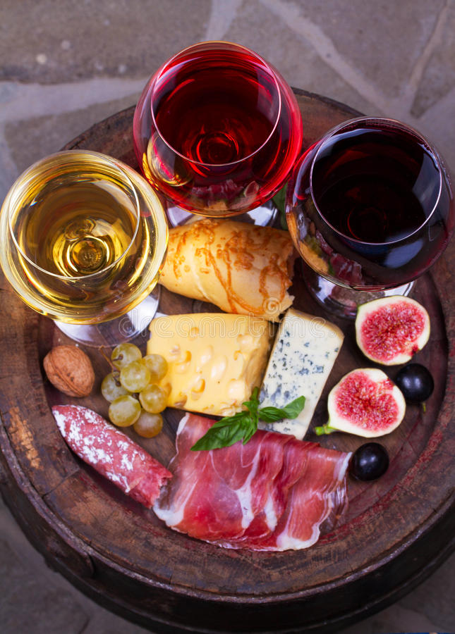 Red, rose and white glasses and bottles of wine. Cheese, fig, grape, prosciutto and bread on old wooden barrel. View from above royalty free stock images