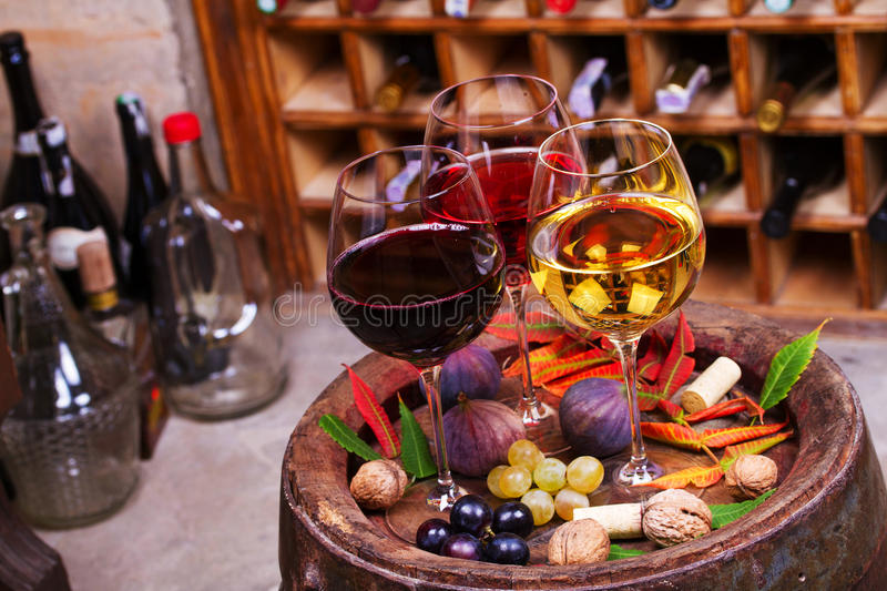 Red, rose and white glasses and bottles of wine. Grape, fig, nuts and leaves on old wooden barrel. royalty free stock photography
