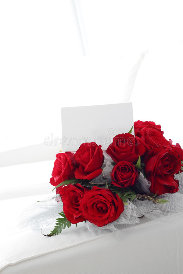 Red Roses. A bouquet of Red Roses with a blank note for words/wishes on a white sofa suitable for wedding theme, thank you or get well soon note stock photo