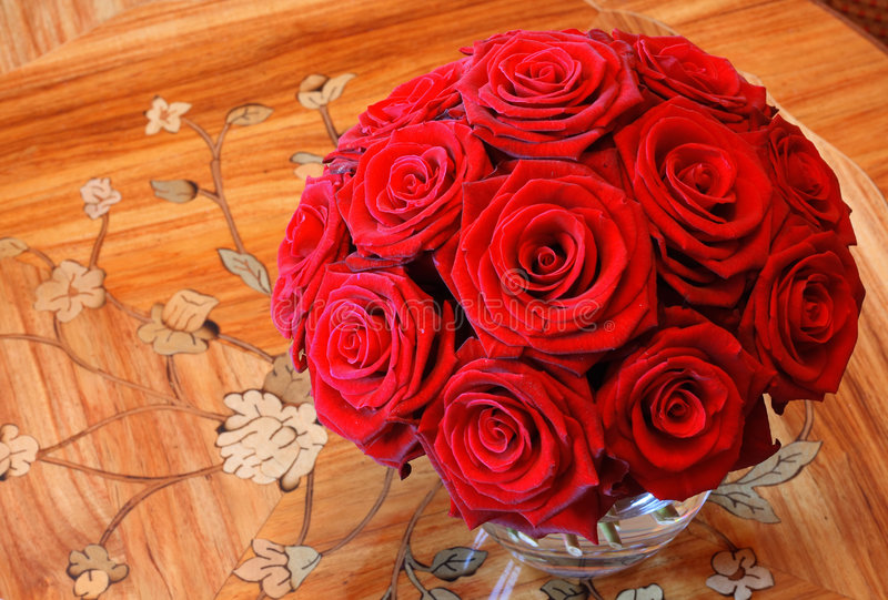 Red Roses. A vase full of red roses in a clear glass vase on a wooden table stock photography