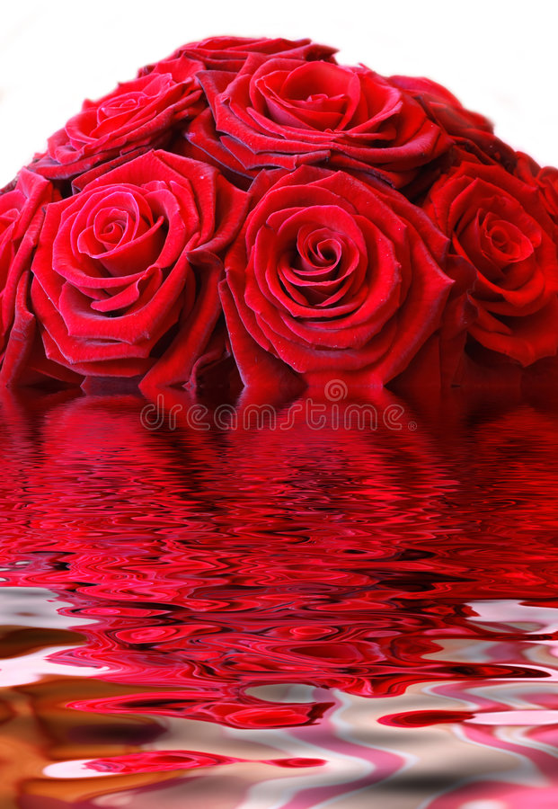 Red Roses. A vase full of red roses in a clear glass vase on a wooden table stock images