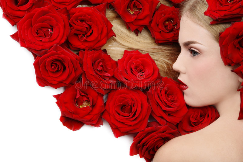 Red roses. Beautiful girl lying on white background with red roses in her blond hair