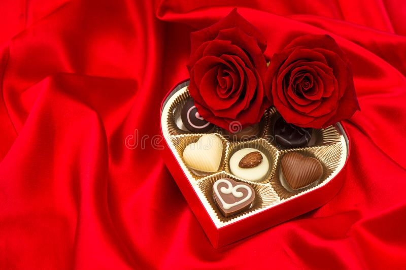 Red roses and assorted chocolate pralines in gift box. Red roses and assorted chocolate pralines in golden heart shaped gift box on satin background royalty free stock images