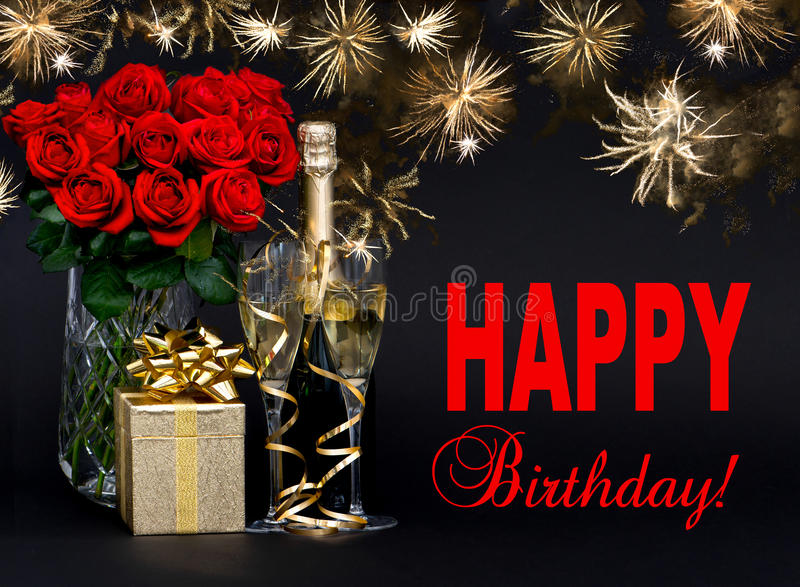 red roses, bottle of champagne, golden gift with beautiful fireworks royalty free stock photography